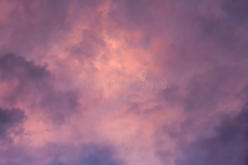 Pink, purple, orange golden glow of clouds at sunset against blue sky ideal as nature background royalty free stock images