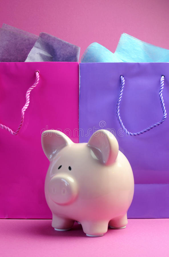 Pink and purple shopping bags with piggy bank - vertical. stock image