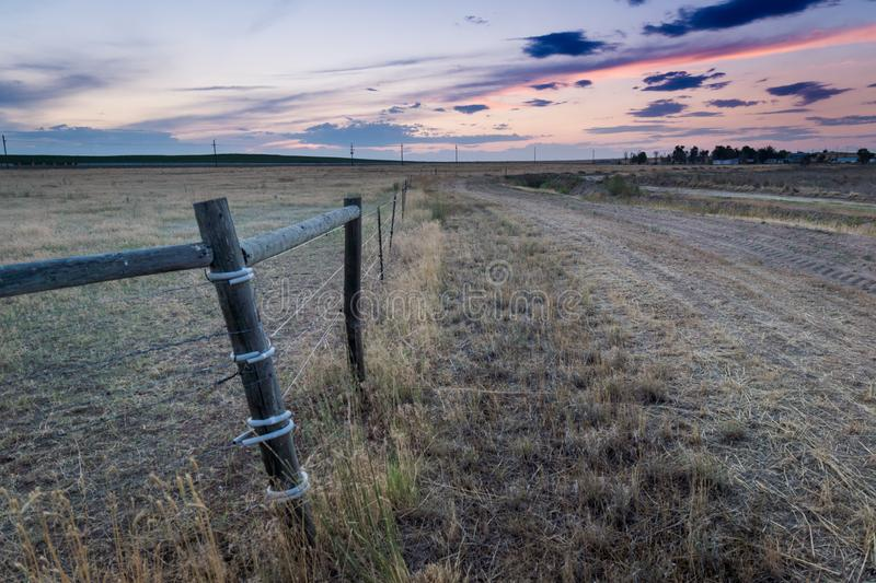 Sunset behind fencing in Eastern Plains Colorado. A pink and purple sunset behind wooden fencing and fields in eastern plains Colorado stock image