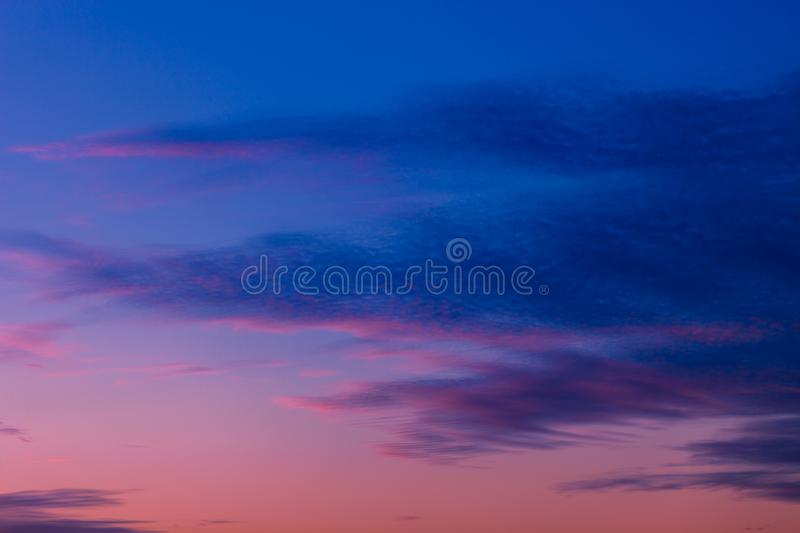 Pink and purple sunset sky with clouds painted in dark tones of blue stock images