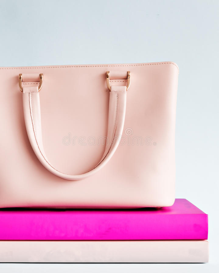 Pink purse over books stock photos