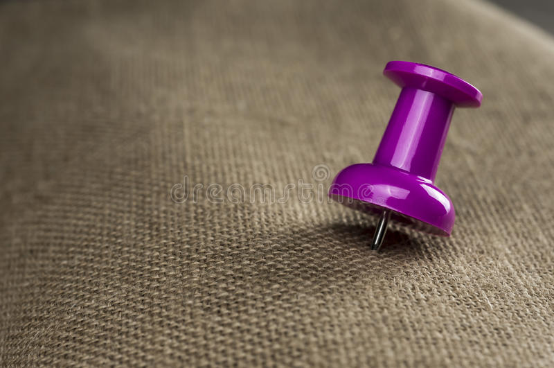 Pink push pin. Macro shot of a pink push pin on hessian cloth royalty free stock photography