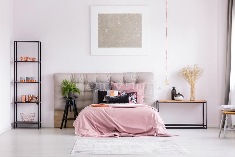 Stylish bedroom with metallic design. Pink quilt on bed with patterned pillows and copper lamp in stylish bedroom interior with metallic design royalty free stock photos