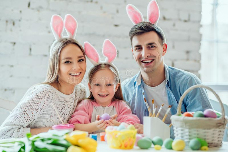 Pink rabbit ears add a festive atmosphere.Happy family paint easter eggs together.Little girl holding easter egg in hands royalty free stock images