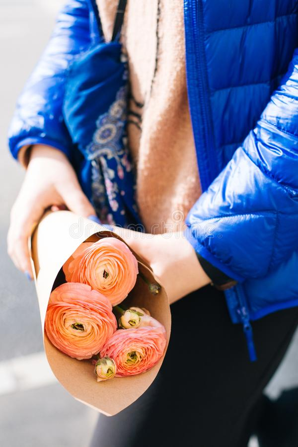 Pink Ranunculus Flower Bouquet on Persons Hand Wearing Blue Zip-up Jacket stock image