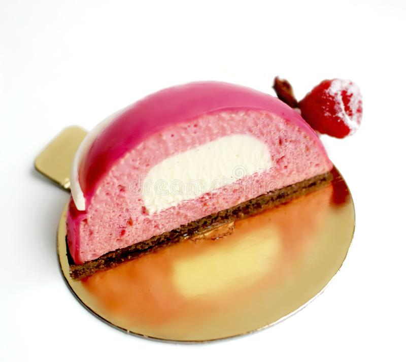 Pink raspberry mousse dessert half with white vanilla insertion on golden coaster stock images