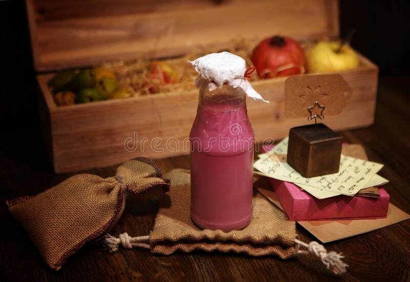 Pink raspberry Smoothie at the bottle. Colorful drink, milk shake in bottle with fresh vegetables and superfoods on a wooden. Pink Smoothie at the bottle royalty free stock image