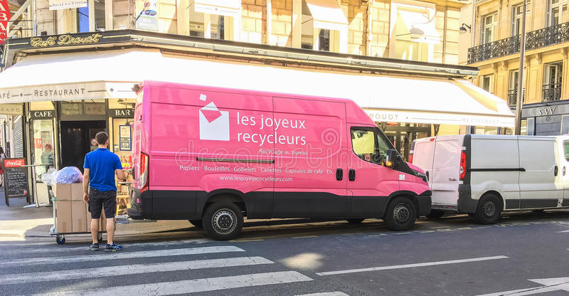 Pink recycling company truck in paris, france. Bright pink recycling company truck parked on Paris street; 'the joyous recyclers royalty free stock photos