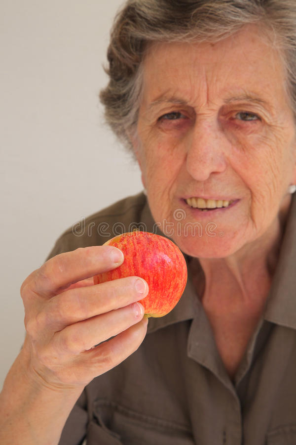 A pink red apple in the hand of old woman stock photo