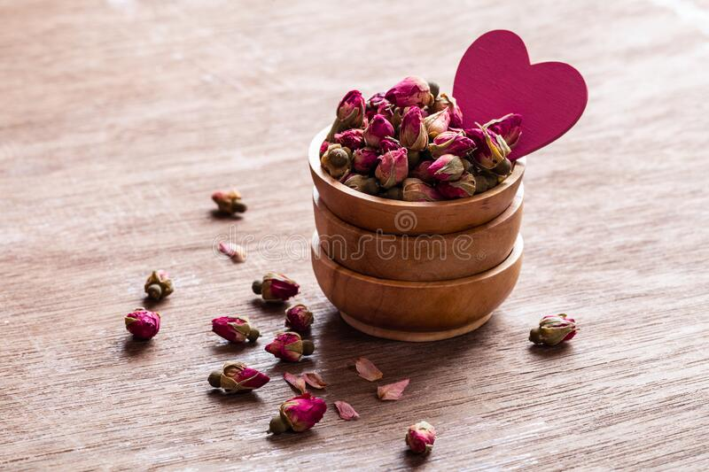 Pink red dried rose buds in wooden bowl with petals and heart shape decoration on old wooden background. Copyspace. Healthy exotic asian organic tea. Love to royalty free stock images