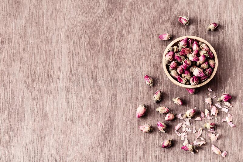 Pink red dried rose buds in wooden bowl with petals on old wooden background copyspace top view. Healthy exotic asian organic tea royalty free stock photography