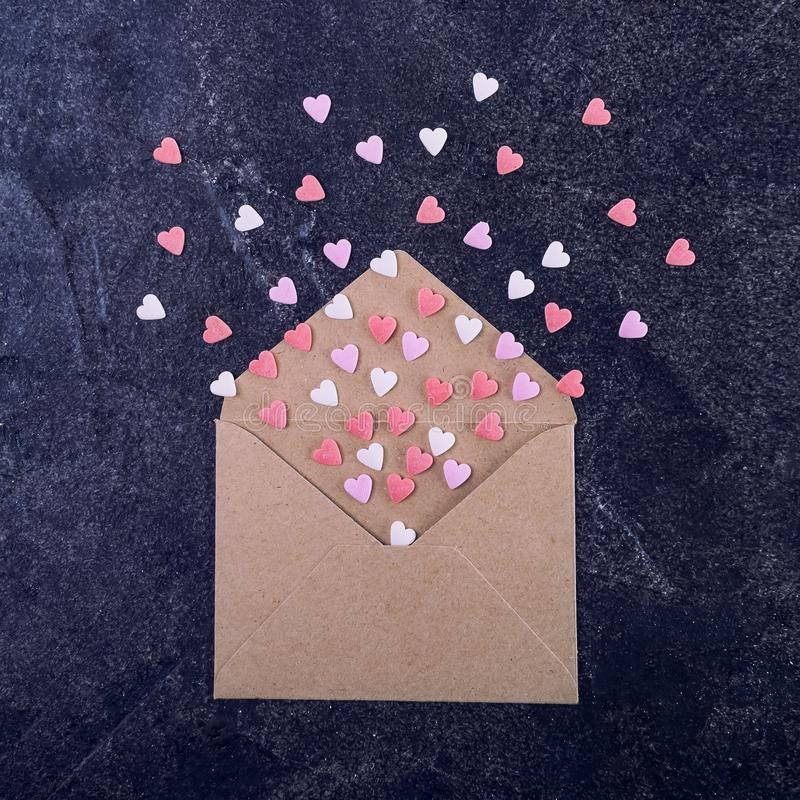 Pink, red and white sweets sugar candy hearts fly out of craft paper envelope on the dark stone background . Valentine day concept stock photography