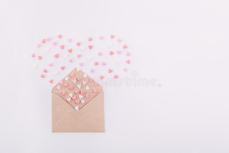 Pink, red and white sweets sugar candy hearts fly out in the form of heart from craft paper envelope on the white background . Val stock photography