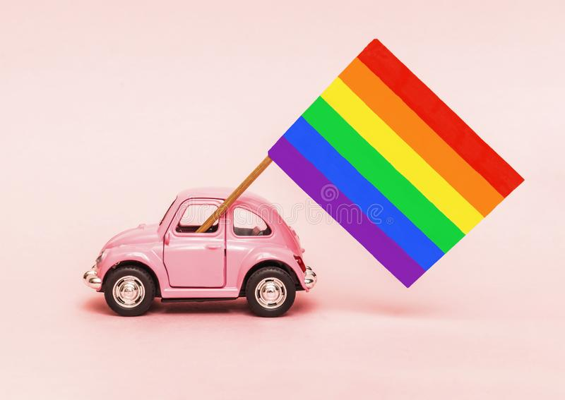Pink retro toy car delivering bright rainbow gay flag on soft pink backgraund. Concept of gay parade, LGBT community and. Celebrating Pride royalty free stock image
