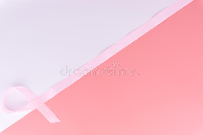 Pink ribbon breast cancer on pink and white background with copy space for text. Flat lay, top view royalty free stock image