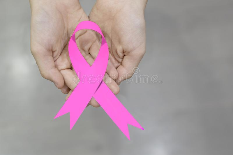 Pink ribbon in the hands. royalty free stock images