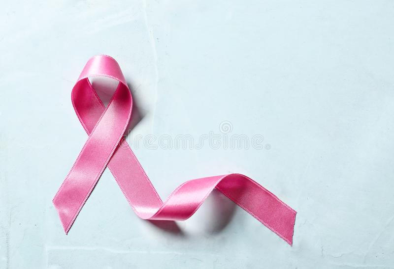 Pink ribbon on light background. Breast cancer awareness concept royalty free stock photo