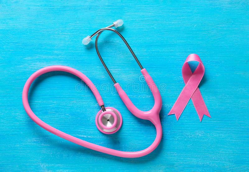 Pink ribbon and stethoscope on color background. Breast cancer awareness concept stock photos