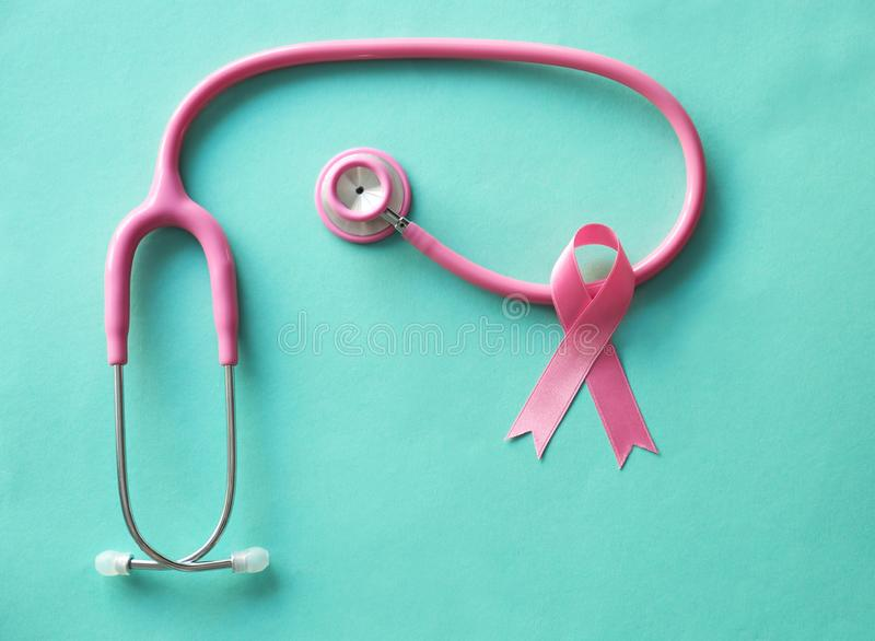 Pink ribbon and stethoscope on color background. Breast cancer awareness concept stock image