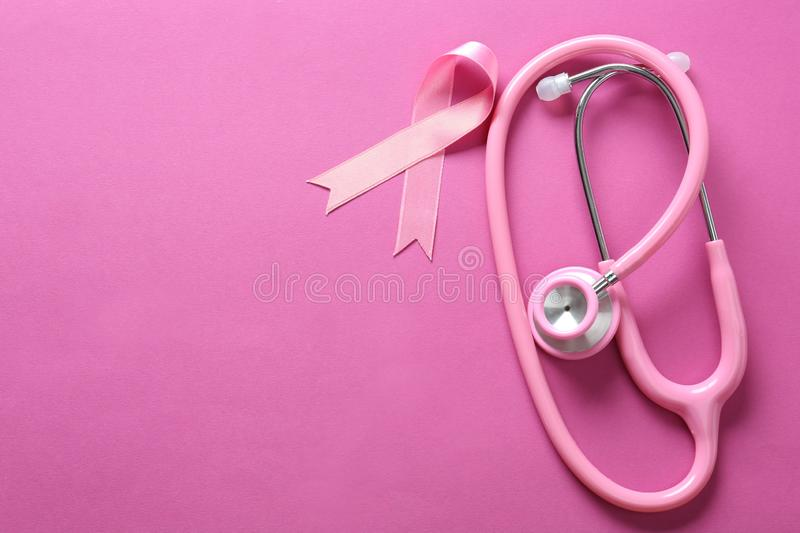 Pink ribbon and stethoscope on color background. Breast cancer awareness concept royalty free stock photography