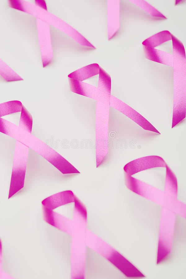 Pink Ribbon - Symbol of Breast Cancer Awareness. Closeup image of many pink ribbons next to each other over white, symbols of breast cancer awareness royalty free stock photo