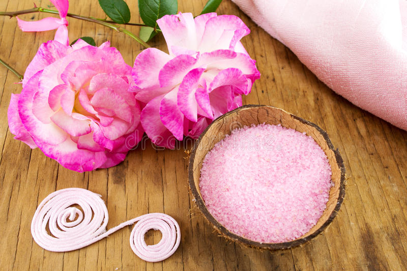 Pink rose and bath salt in a bowl. Pink rose and bath salt in a coconut bowl stock image