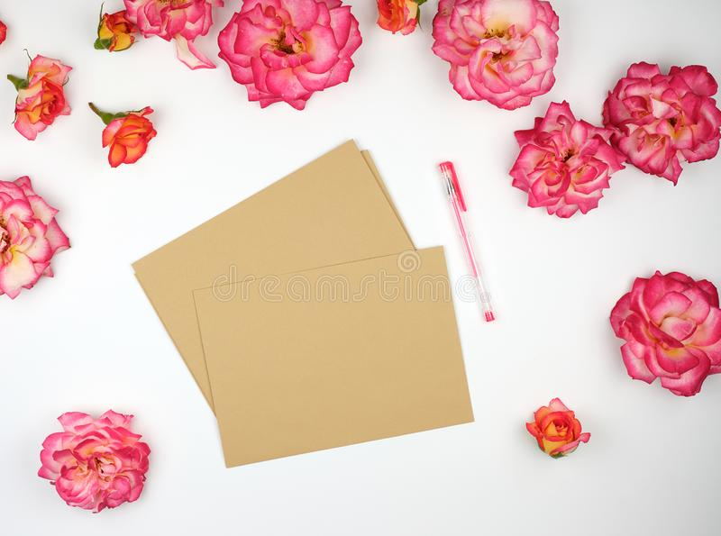 pink rose buds and a brown paper envelope royalty free stock photography