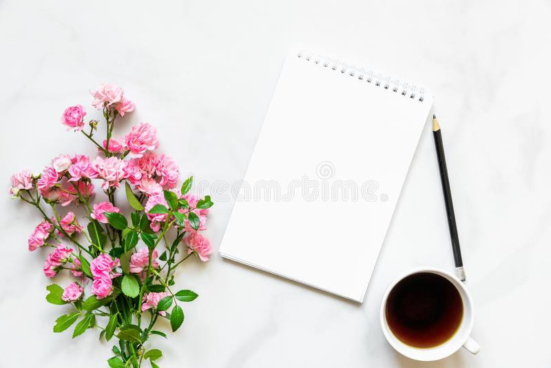 Pink rose flowers bouquet, coffee cup and blank paper notebook to put your text on white marble background. mock up royalty free stock photos