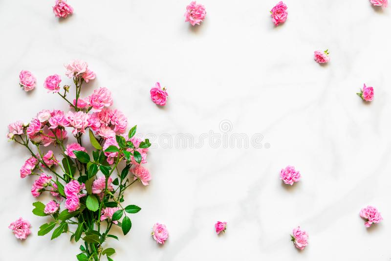 Pink rose flowers bouquet with frame made of flower buds with copy space on white marble table. flat lay. top view royalty free stock photo