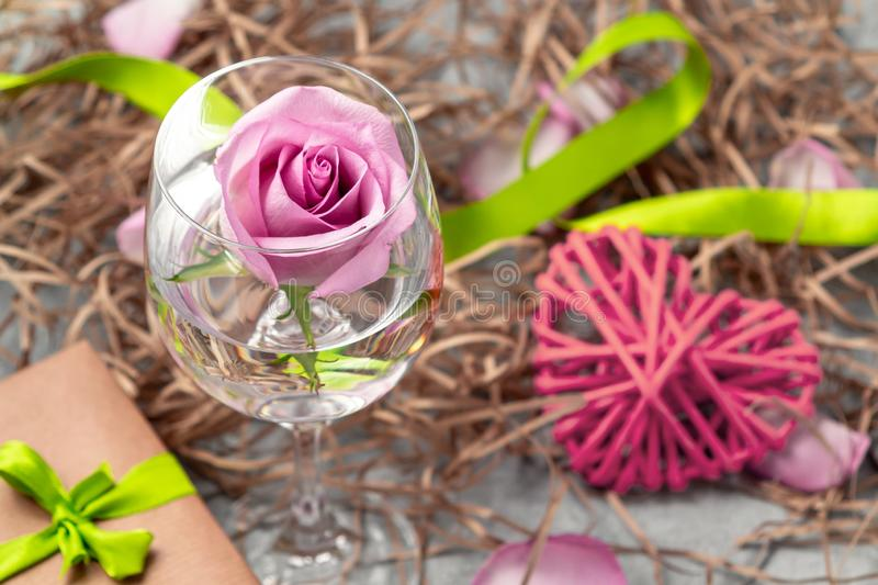 Pink rose in a glass with water and decorations on the table royalty free stock photos