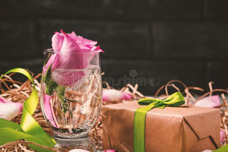 Pink rose in a glass with water and decorations on the table royalty free stock photography