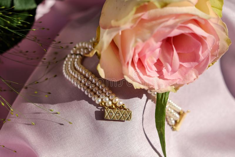 Pink Rose and Gold Beaded Jewelry royalty free stock photos