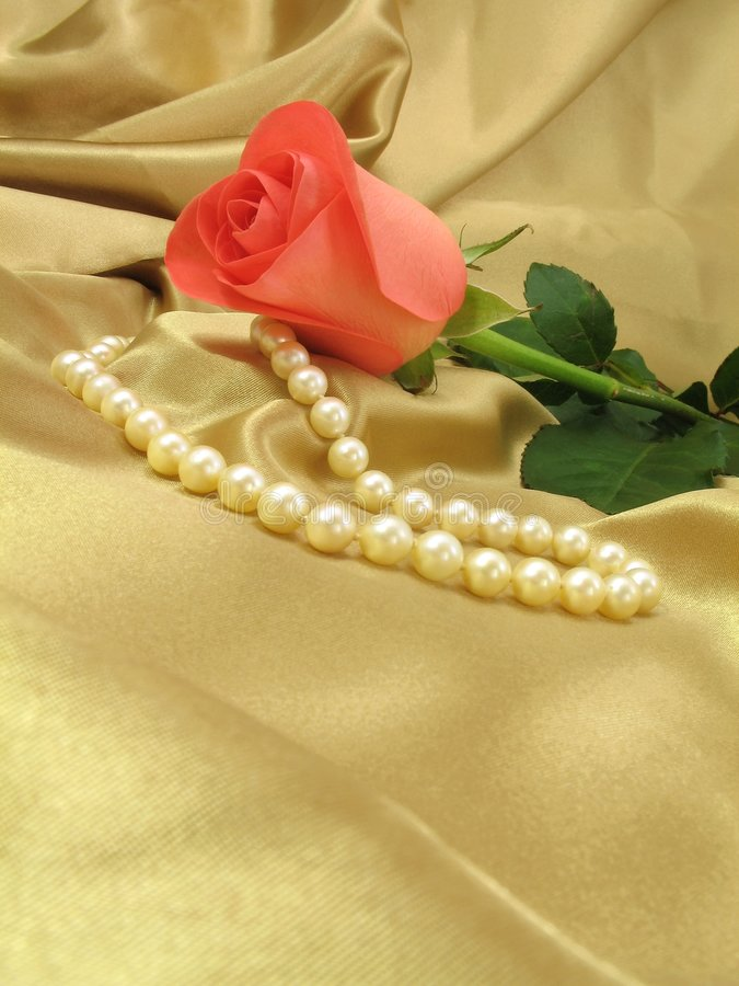 Pink rose and pearls on gold satin. A delicate pink rose and a string of pearls on a loosely laid sheet of gold satin, with copy-space. A delicate pink rose and stock images