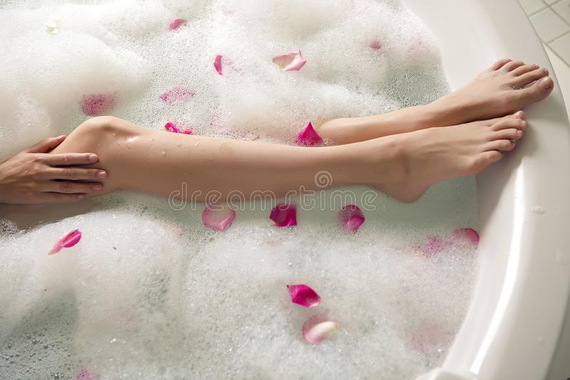 Pink rose petals in a round tub. With legs girls royalty free stock photography