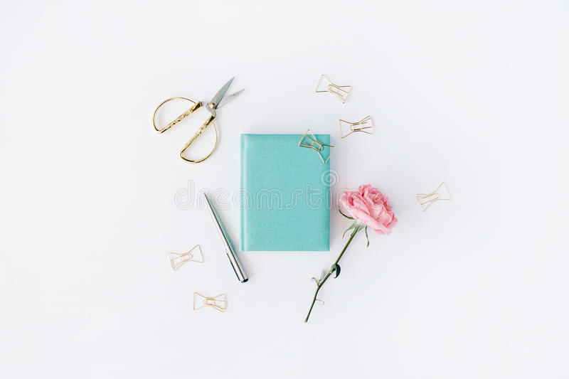 Pink rose, scissors, golden clips, mint diary and pen stock image