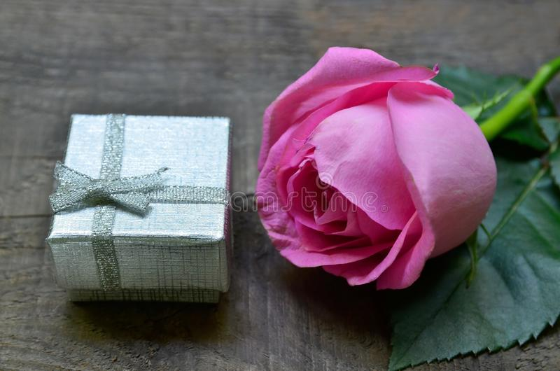 Pink rose and silver gift box on old wooden background. Mother´s Day,Women`s Day,Birthday greeting card concept. Soft focus stock photo