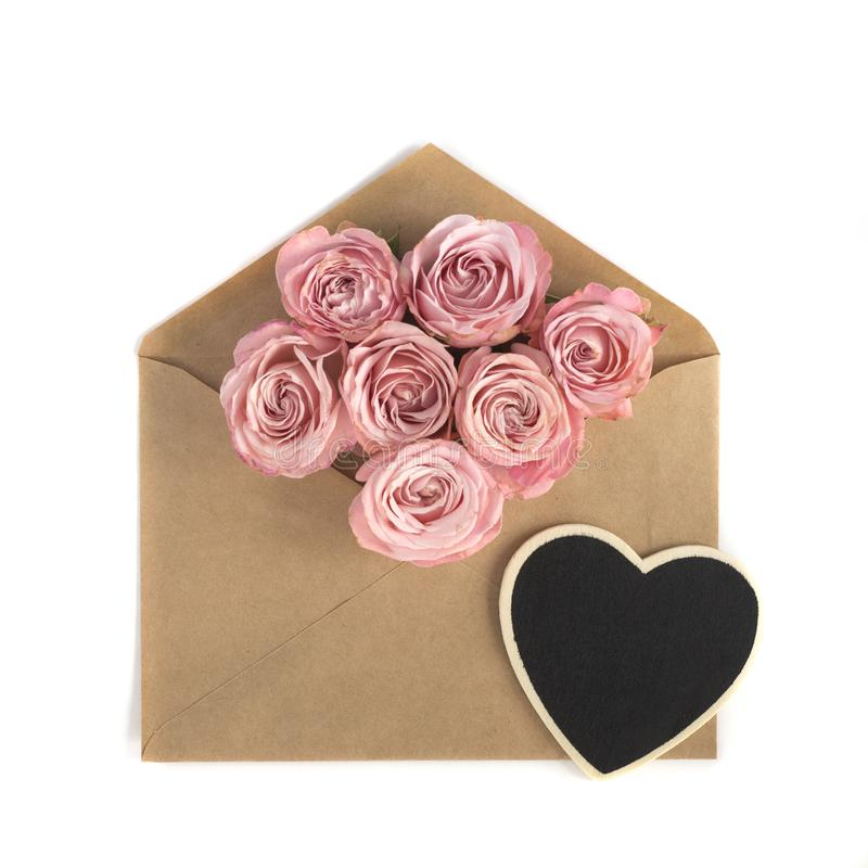 Pink roses and black heart in the craft paper envelope on the white background. Flower greeting card stock image