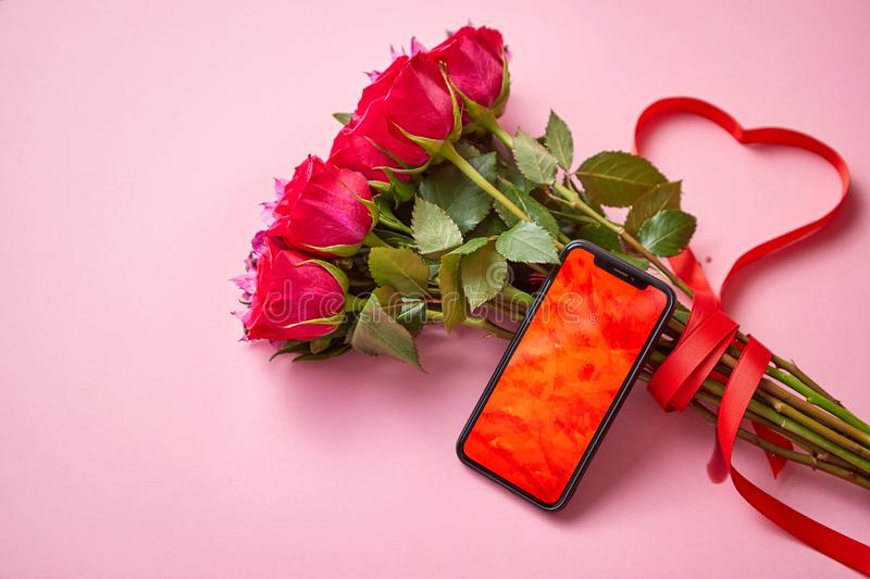 Pink roses bouquet with hart shaped bow and mobile phone with copy space screen stock photography