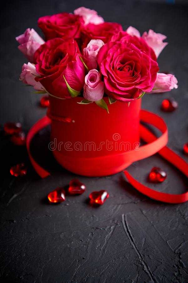 Pink roses bouquet packed in red box and placed on black stone background royalty free stock image
