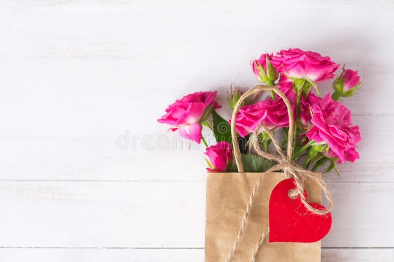 Pink roses in craft paper bag with red heart stock photos