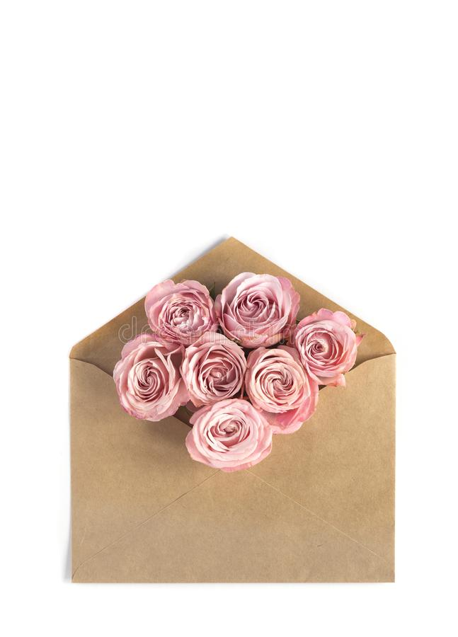Pink roses in the craft paper envelope on the white background. Flower greeting card royalty free stock images