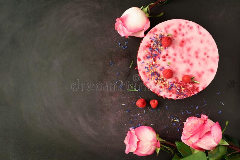 Pink roses and delicious raspberry cake with fresh berries, rosemary, dry flowers on dark vintage background. Copy space for your. Text. Vegetarian, vegan food stock image