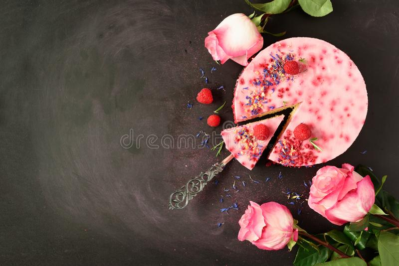 Pink roses and delicious raspberry cake with fresh berries, rosemary, dry flowers on dark vintage background. Copy space for your. Text. Vegetarian, vegan food royalty free stock images