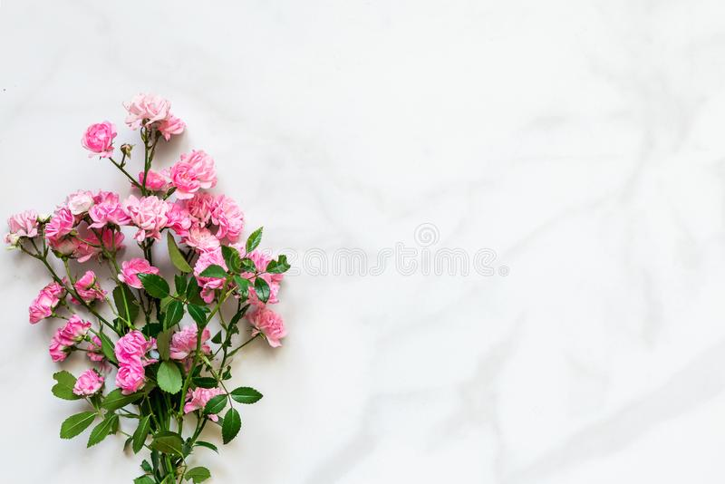 Pink roses flowers bouquet over white marble table with copy space. top view. mock up. Nature concept royalty free stock image