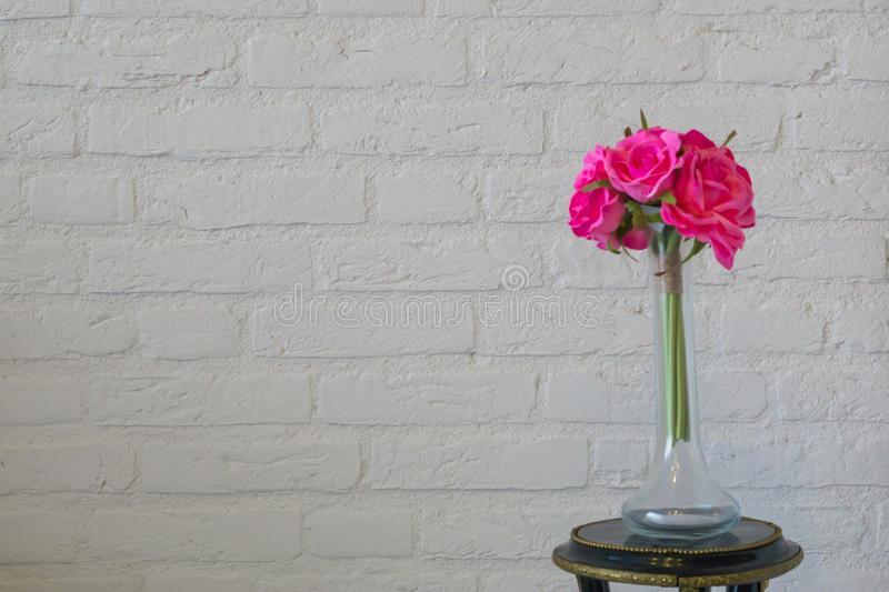 Pink roses in a glass vase on a white brick wall, valentines day or interior background royalty free stock photography