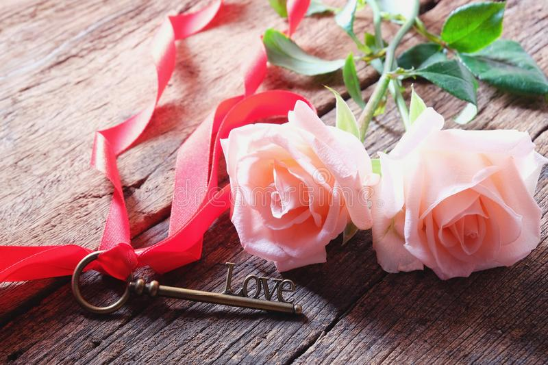 Pink roses and Love key shape on vintage wooden floor under soft warm light. Backdrop for Valentine's day. Love concept. Copy space stock images