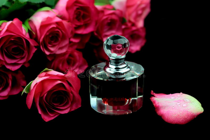 Pink roses and perfume. On black background stock photos