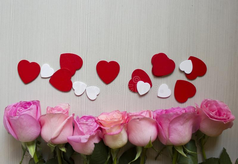 Pink roses, red and white hearts over wooden background. Valentines day background. royalty free stock images