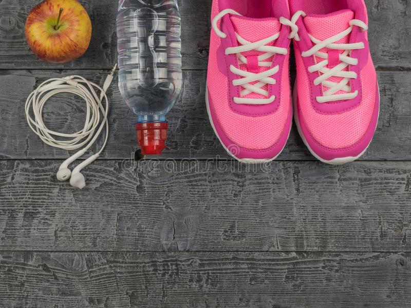 Beautiful pink sneakers, headphones, water and apples on a wooden floor. View from above. Pink running shoes for fitness classes at the gym and a ripe Apple on royalty free stock photo