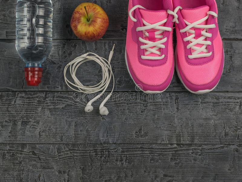 Beautiful pink sneakers, headphones, water and apples on a wooden black floor. View from above. Pink running shoes for fitness classes at the gym and a ripe stock photography